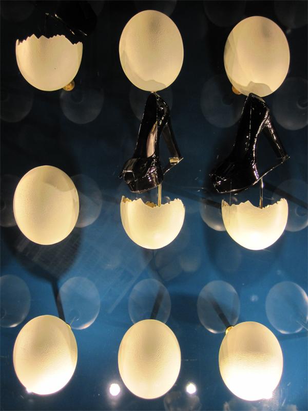 vetrina spettacolo con scarpe nere che escono da uova su sfondo blu